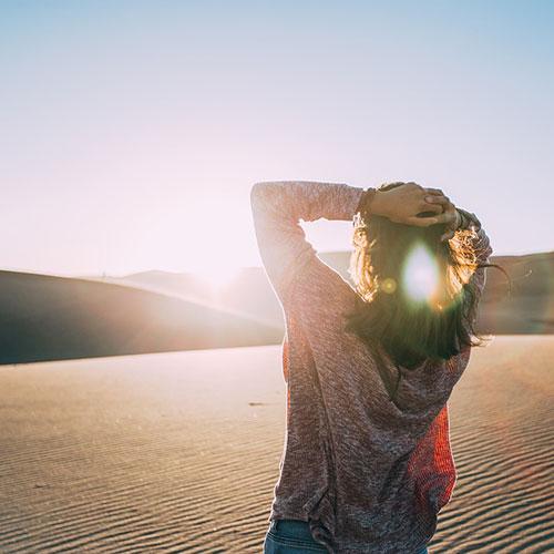 Femme face au soleil levant sur l'Erg Chebbi